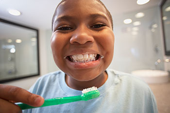 Child smiling with a wide grin as he brushes teeth.