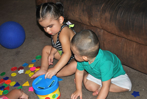 Two toddlers playing with a puzzle game