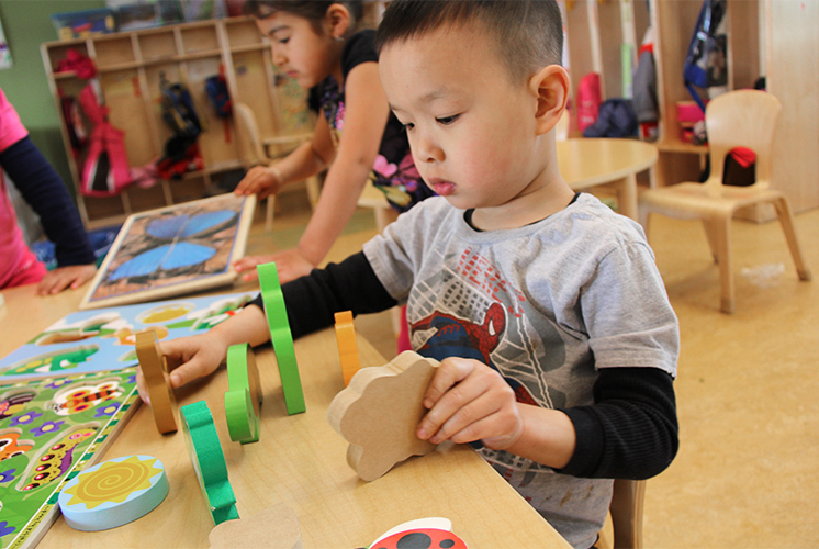 A boy plays with wooden shapes
