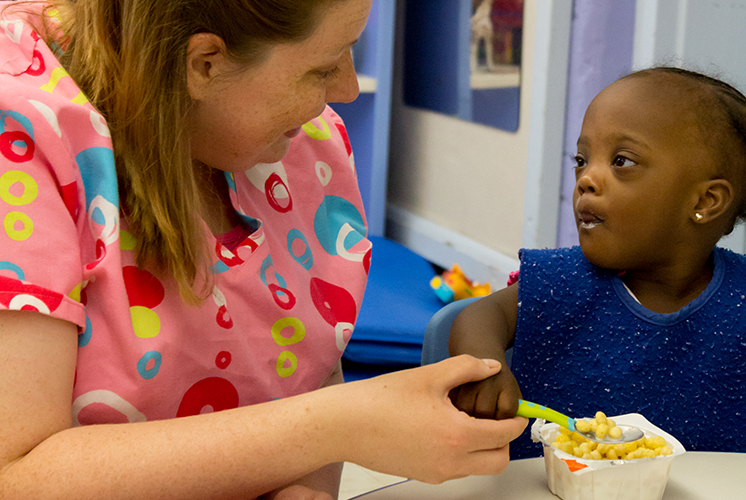 caregiver helps girl eat cereal