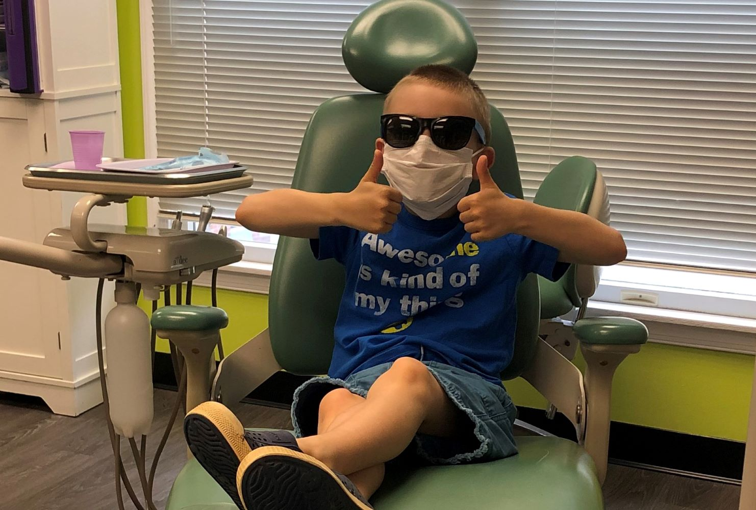 Child in dentist chair wearing a cloth face mask.