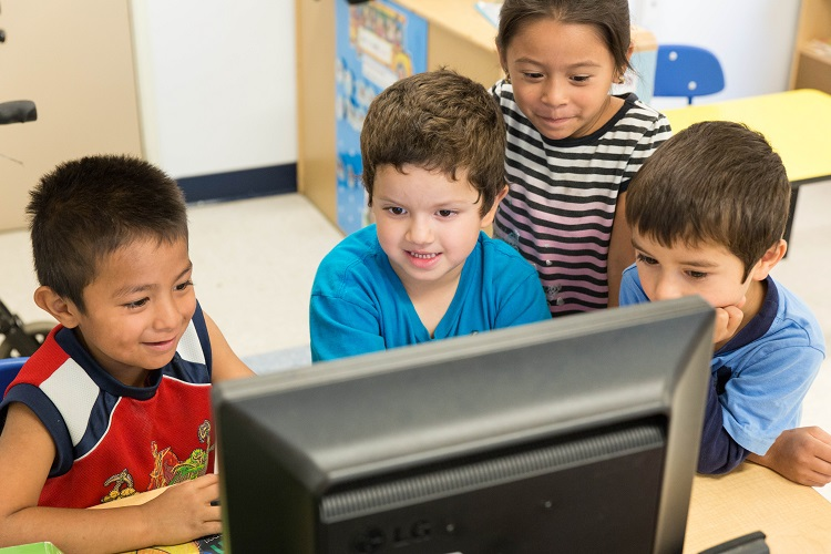 children watching to a computer monitor