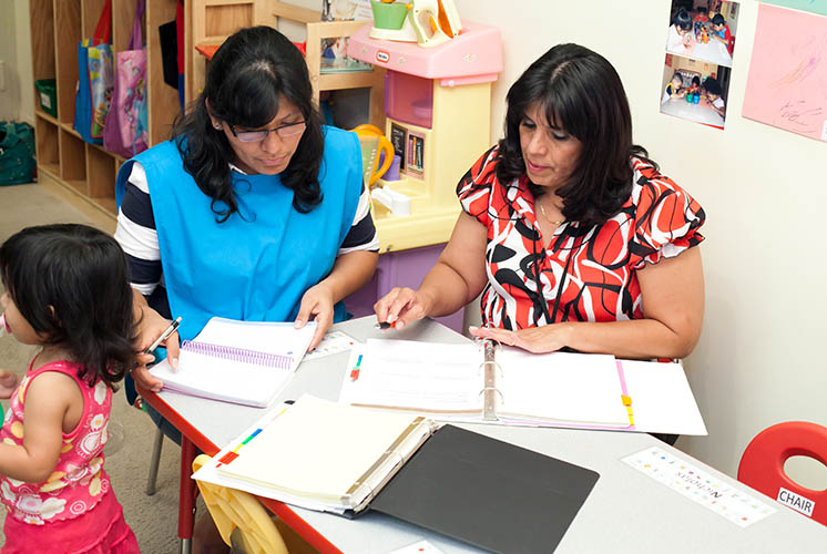 two women consult papers and files while a child plays nearby
