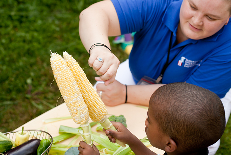 a boy holds ears of corn at a table with a teacher