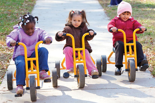 three children on tricycles