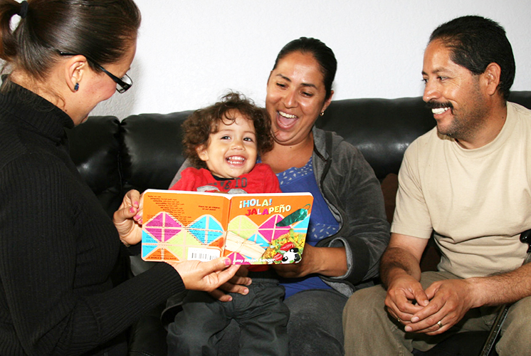 A home visitor reads a book with a family
