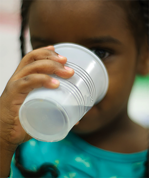 Young girl drinking water out of a plastic cup
