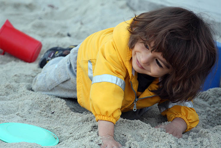 a girl playing outside in sand