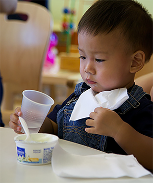 Little boy eating yogurt and drinking water