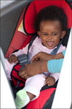 Young girl being securely buckled into her car seat.