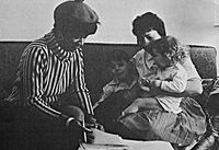 Two adults hold two children on a couch in a vintage photo