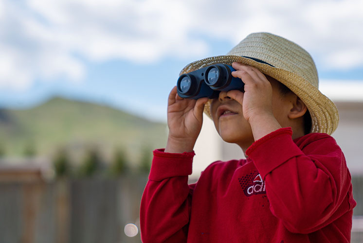 A boy looks at the sky through binoculars