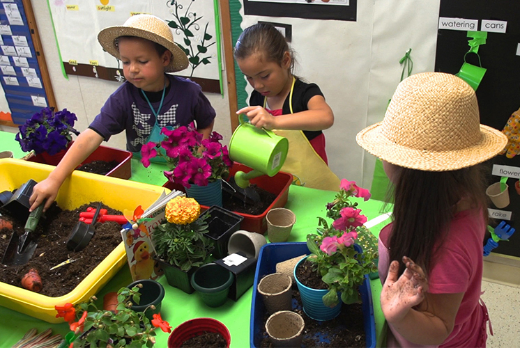 Children gathered around table full of plants and gardening tools