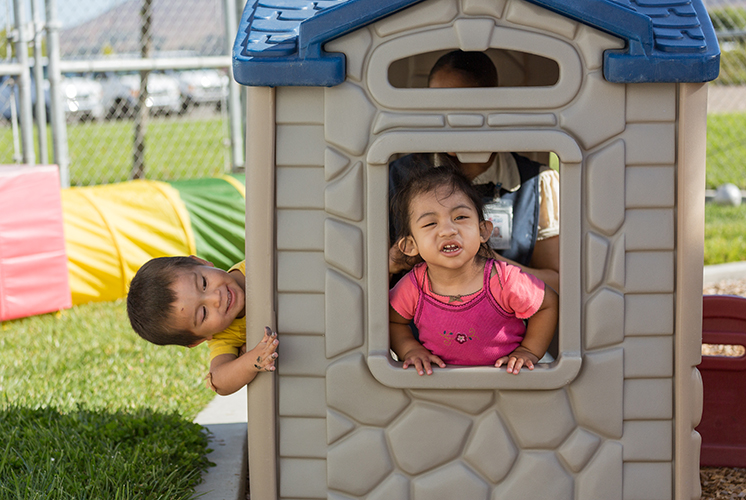 two children play in playground house