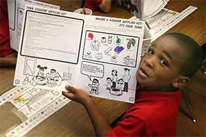 Child holding up the Know the Signs Worksheet