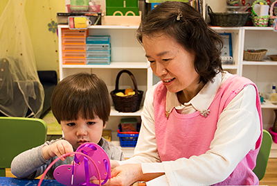 Teacher helping a toddler student with an activity