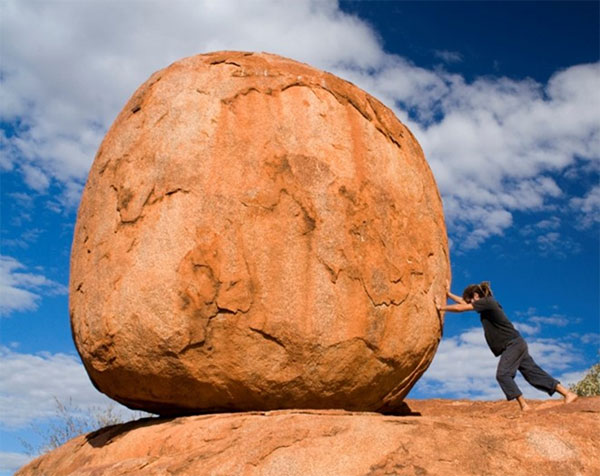 Woman trying to move a boulder