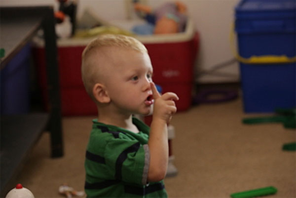 Toddler boy holding up a finger to be quiet