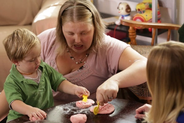 Teacher showing a child how to cut play doh