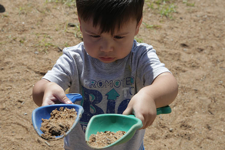 a boy lifts two plastic scoops of dirt and sand
