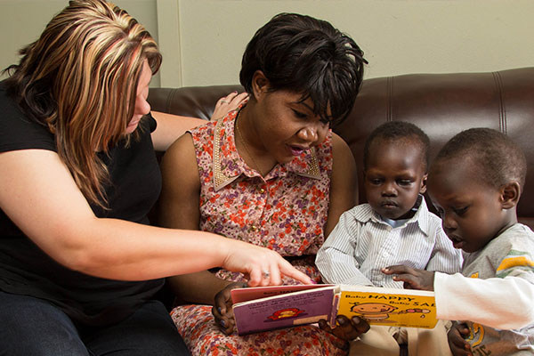 Home visitor helping a parent and child read a book