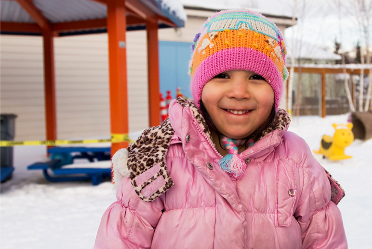 A smiling girl stands in a snow covered playground
