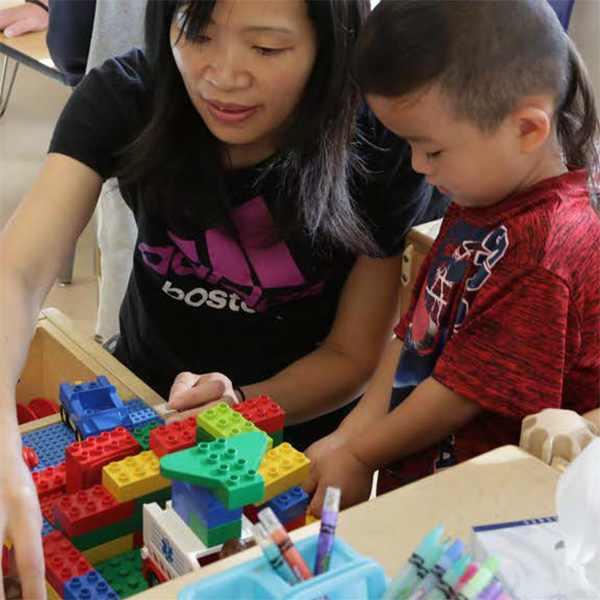 Teacher showing a toddler boy how to stack blocks