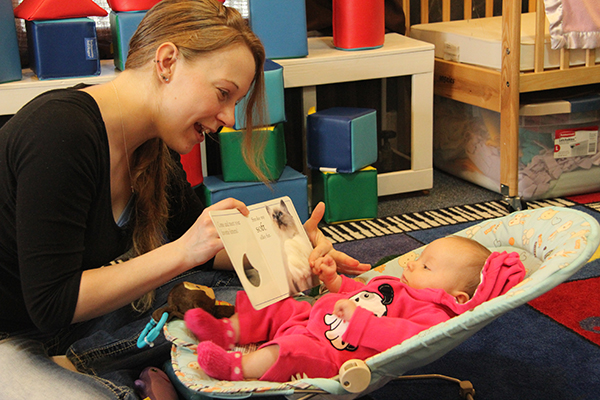 Teacher reading book to infant