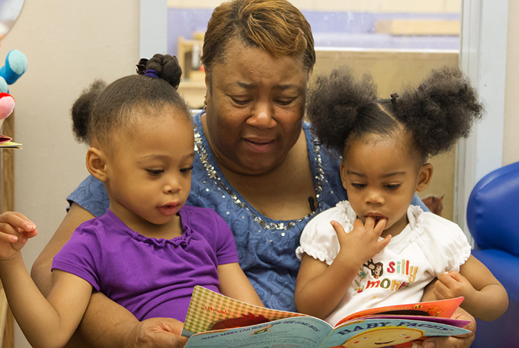 A teacher reads to two girls on her lap