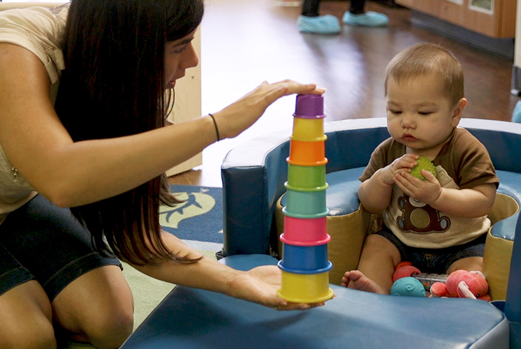 A teacher shows stacking cups to a toddler