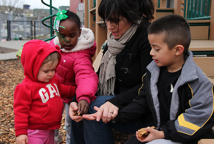 A teacher and three students examine leaves together outside