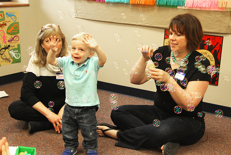 Teachers play with a toddler using bubbles