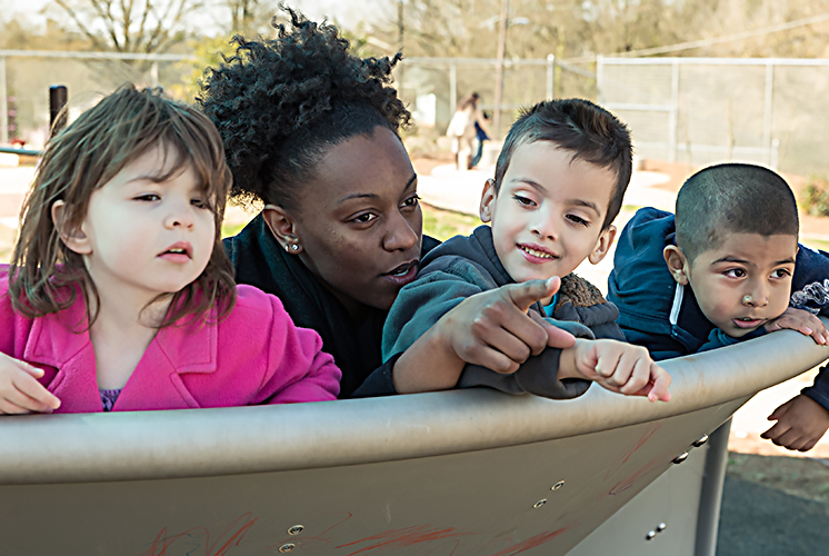 three kids and a teacher playing on the playground