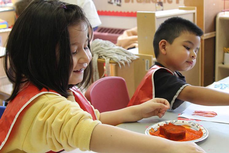 A boy and girl play with paint and sponges at a table