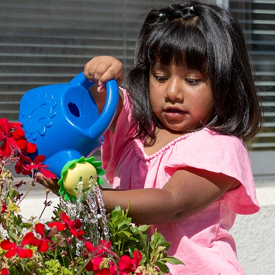 a girl waters flowers