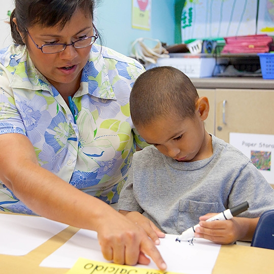 teacher helping boy with marker